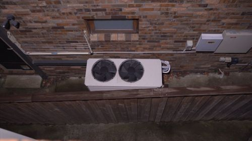 The Huang family say their neighbour's loud air conditioner, which sits directly beneath their bedroom window, is affecting their health.