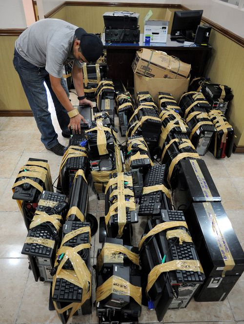 A National Bureau of Investigation (NBI) agent inspects confiscated desktop computers allegedly used for cybersex crime,