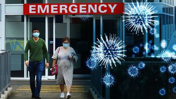 Two people wearing face masks walk out of the emergency entrance at Westmead Hospital, in Sydney's west.