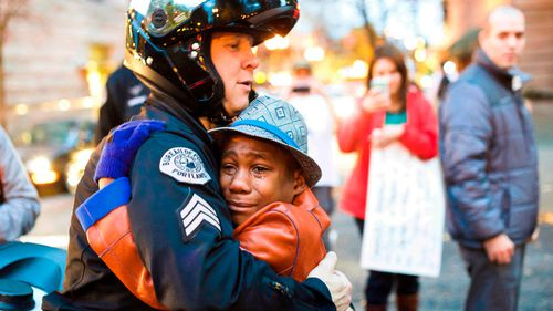 Portland police Sgt Bret Barnum and Devonte Hart, 12, hug at a rally in Portland, Oregon in 2014. (AP)