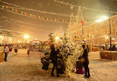A woman takes a photo of her friend as snow falls on Christmas lights in Moscow, Russia. (Sefa Karacan/Anadolu Agency/Getty)