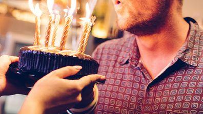 Woman holding cake for man at birthday celebration.