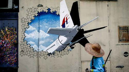 A man walks in front of a Malaysia Airlines flight MH370 mural painted on a wall at a street in Shah Alam, outside Kuala Lumpur, Malaysia. (Photo: AP).