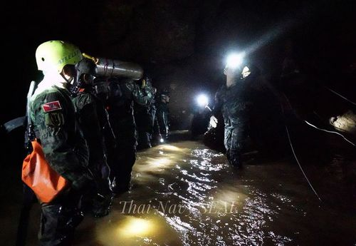 Rescuers are seen here taking supplied into the cave.