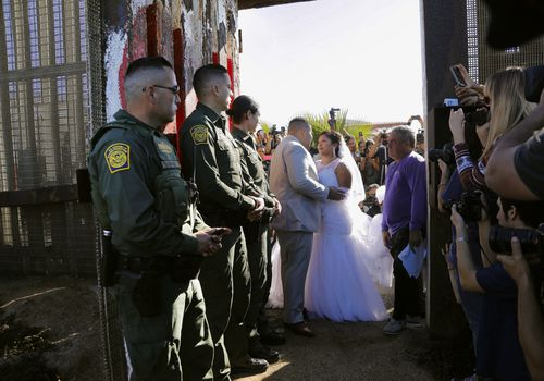 """Brian Houston, of Rancho San Diego, center left, and Evelia Reyes, right, of Tijuana, Mexico, look at each other in their wedding at the """"Door of Hope,"""" part of the border fence between the U.S. and Mexico. (Howard Lipin//The San Diego Union-Tribune via AP)"""