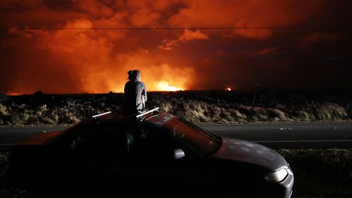 Brittany Kimball watches as lava erupts from from a fissure near Pahoa, Hawaii, Saturday, May 19, 2018. (AP)