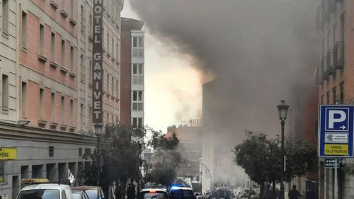Smoke rises from a building and rubble scattered in Toledo Street following a explosion in downtown Madrid, Spain, Wednesday, Jan. 20, 2021