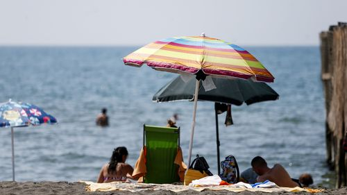 People enjoy a day at the beach, in Ostia, in the outskirts of Rome, Saturday, Aug. 14, 2021.  (Cecilia Fabiano/LaPresse via AP)