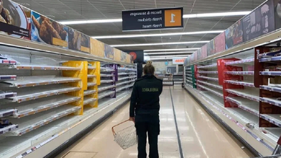 Paramedic staring at empty shelves in a supermarket in the UK.