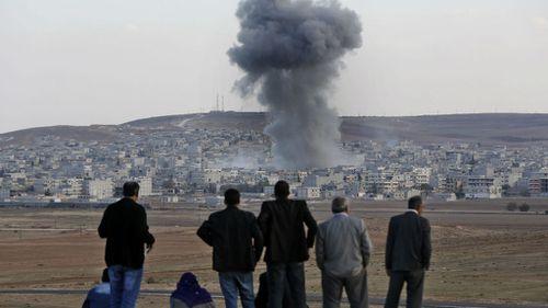 Locals watch on as US-led air strikes rain down on Kobane. (AAP)