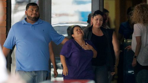 People react outside the unification centre at the Alamo Gym. Picture: AP