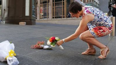 Mourners take time out before work to pay their respects with small bunches of flowers. (Twitter/@vancouverSun)