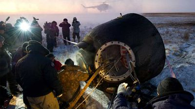Russian support personnel work to help get Expedition 29 crew members out of the Soyuz TMA-02M spacecraft shortly after the capsule landed in November 2011. (NASA)