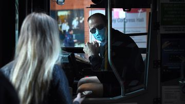 A bus driver wearing a mask talks to a passenger on Elizabeth street in Sydney's CBD