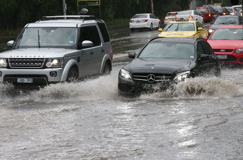 Traffic passes through flood water on Wellington Parade in East Melbourne as forecasters predict flash flooding and storm damage across Victoria.