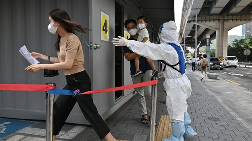 A health official wearing protective gear guides visitors at a coronavirus testing station in Seoul on August 18, 2020.