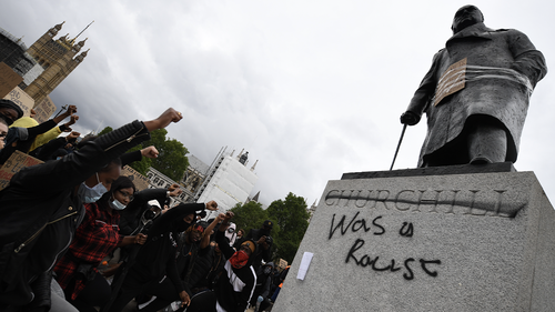 """Protesters raise their fists in Parliament Square Garden around the statue of Winston Churchill which has graffiti with the words """"was a racist"""" outside the Houses of Parliament in Westminster during a Black Lives Matter protest on June 07, 2020 in London, United Kingdom."""