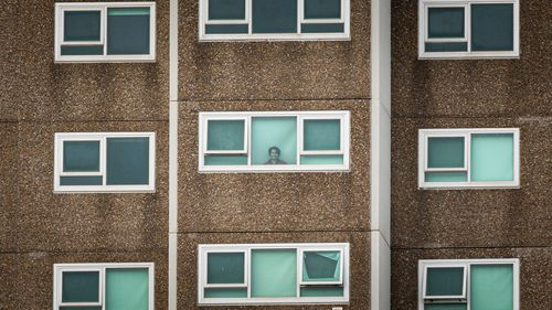 A lone woman is seen looking out the window of her apartment at the North Melbourne Public housing flats on July 05, 2020 in Melbourne, Australia. Nine public housing estates have been placed into mandatory lockdown and two additional suburbs are under stay-at-home orders as authorities work to stop further COVID-19 outbreaks in Melbourne.