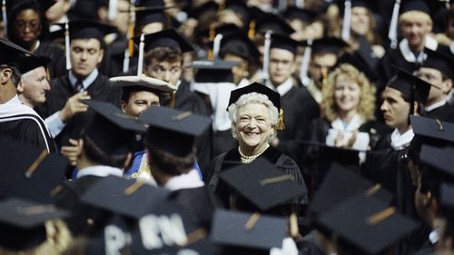 Mrs Bush is remembered as a fierce literacy advocate. She is pictured with graduates at St Louis University in 1990. (AAP)