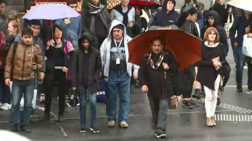 Pedestrians struggle to avoid the rain in Melbourne's CBD. (9NEWS)