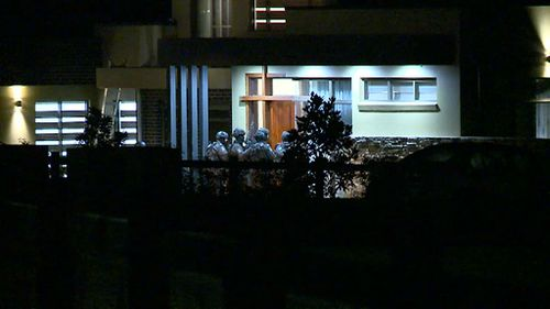 Heavily armed police approach the home. (9NEWS)