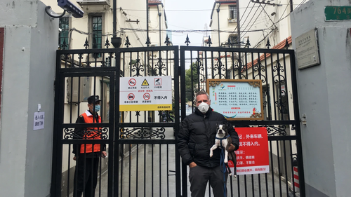 Michael Smith (and his dog Huey) outside his compound in Shanghai.
