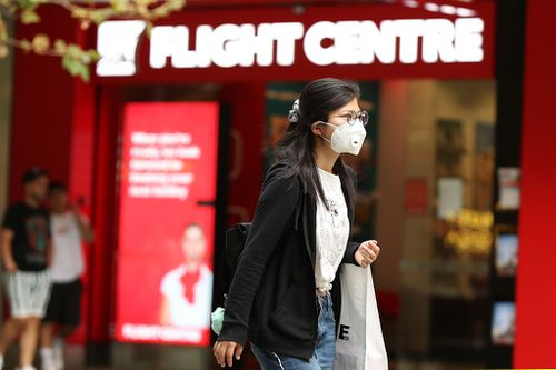 A woman is seen wearing a mask while walking down Murray Street mall on March 27, 2020 in Perth, Australia.