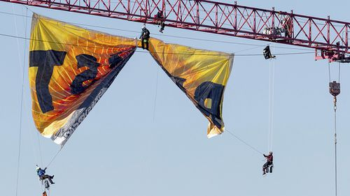 Protesters chained themselves to the crane while others attached to wires unfurled the banner. (AAP)