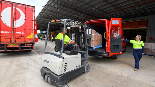 Workers pack Australia Post delivery trucks and vans