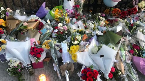 People have been leaving flowers, balloons and cards at the school since yesterday afternoon. (9NEWS)