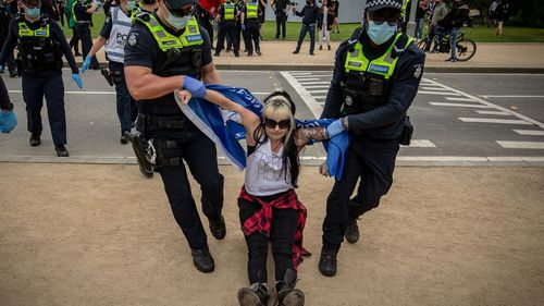 A woman is detained by members of Victoria Police on October 23, 2020 in Melbourne, Australia.
