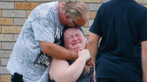 A man hugs a woman outside the Alamo Gym where parents wait to reunite with their children. Picture: AP