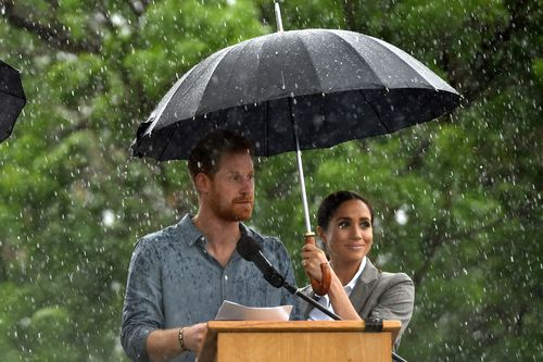 Prince Harry later gave a moving speech - under an imbrella held by wife Meghan - as he spoke of the town's strength.