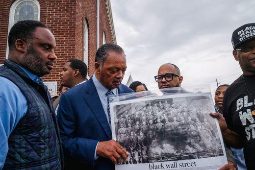 Rev. Jesse Jackson views a Black Wall Street poster board alongside community residents during a Prayer Wall memorial gathering.