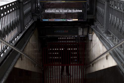 A subway employee stands in the closed entrance of the Buenos Aires's subway during a blackout, in Buenos Aires, Argentina.  (AP Photo/Tomas F. Cuesta)