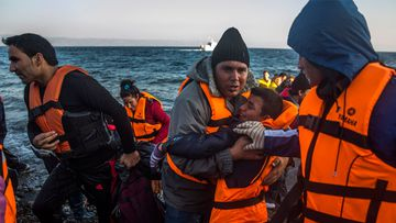 Refugees and migrants disembark from a dinghy after their arrival from the Turkish coast to the northeastern Greek island of Lesbos. (AAP)