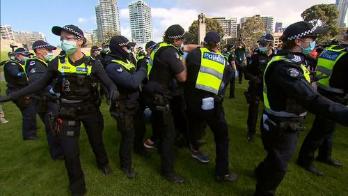 Police attemt to make an arrest during anti-lockdown protests.