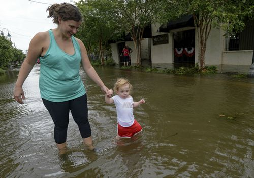 Stephanie Barlow and her daughter June Barlow wade through storm surge from Lake Pontchartrain on Lakeshore Drive in Mandeville, Louisiana.