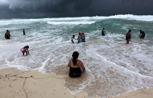 People swim in the turbulent sea at a beach in Cancun, Quintana Roo, Mexico, when the storm moved through the Gulf of Mexico.