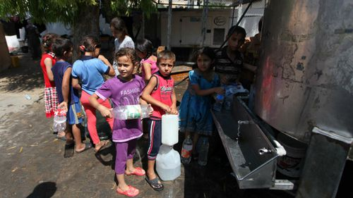 Palestinian children sheltering in a UN school in Gaza line up for water. (Getty)