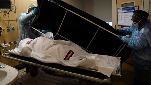 Transporters Miguel Lopez, right, Noe Meza prepare to move a body of a COVID-19 victim to a morgue at Providence Holy Cross Medical Center in the Mission Hills section of Los Angeles Saturday, Jan. 9, 2021. (AP Photo/Jae C. Hong)