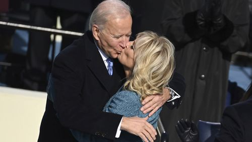 President Joe Biden gets a kiss from first lady Jill Biden after he took the oath office during the inauguration at the U.S. Capitol in Washington, Wednesday, Jan. 20, 2021