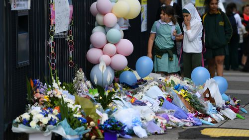 Balloons and flowers are laid as tributes outside the school.