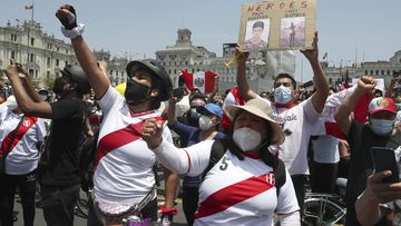 A person holds a sign with photos of two demonstrators killed during protests as people celebrate the resignation of interim president Manuel Merino, at the Plaza San Martin in Lima, Peru.