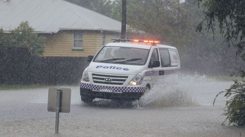A police car drives through floodwaters in South Townsville.