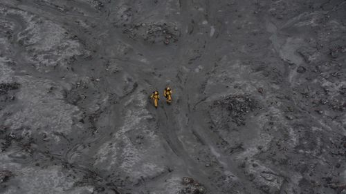 A recovery team wore protective suits to prevent contact with boiling mud and toxic gases.