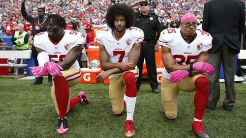 Eli Harold, Colin Kaepernick and Eric Reid kneel during the US National Anthem.