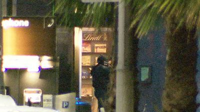 A Special Operations Group officer carrying an assault rifle steps into the Lindt cafe during the raid. (9NEWS)