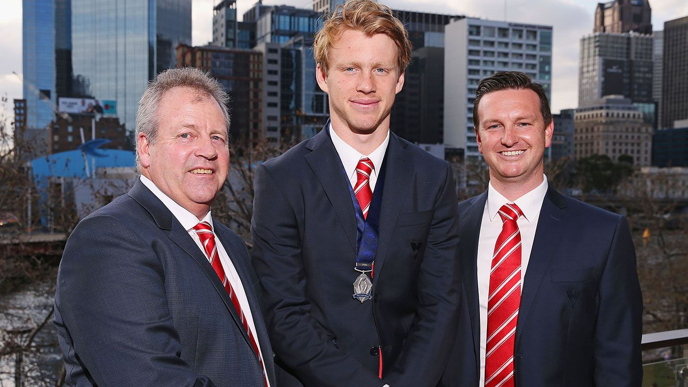Swans recruiting managers Kinnear Beatson (L) and Michael Agresta pose with Rising Star winner Callum Mills of the Swans during the 2016 AFL Rising Star Announcement