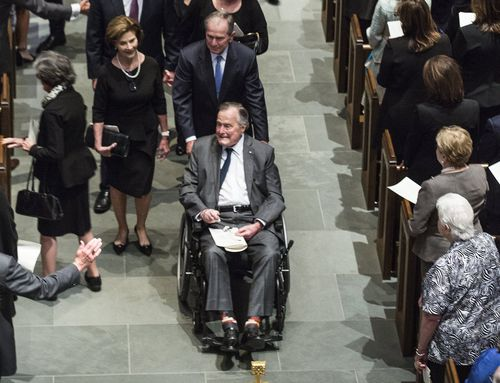 George H.W. Bush is pushed in his wheelchair by son George W. Bush at the funeral. (AAP)